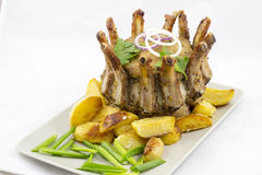 Crown roast of pork with potato wedges Royalty Free Stock Photography