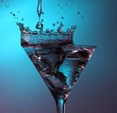 Crown shaped splass in martini glass. Water poured into a martini glass, causing a crown shaped splash royalty free stock photography