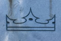 Crown on stone surface. Symbol of might and victory. Close up on a crown, engraved on stone surface. Symbol over the victory over death. Triumph, loyalty and Royalty Free Stock Image