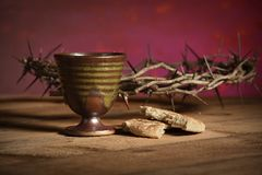 Crown of Thorns, Cup and Bread. Crown of thorns , cup and bread on rustic table royalty free stock photography