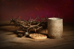 Crown of Thorns, Cup, Nails and Bread. Crown of thorns, cup of wine, bread and nails over wooden table stock photography