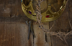 Crown of thorns and gold crown with nails Stock Photos