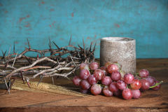 Crown of Thorns Grapes and Cup. Communion table with crown of thorns, cup, grapes and wheat stock image