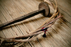 The crown of thorns of Jesus Christ and a nail on the Holy Cross. A depiction of the crown of thorns of Jesus Christ with blood and a nail on the Holy Cross Stock Photos