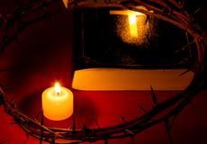 Crown of Thorns of Jesus Christ put on the Bible beside a candle. On a red background. Useful as religious / Easter background Stock Photography