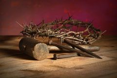Crown of Thorns, Mallet and Nails. Over vintage table over red background royalty free stock image
