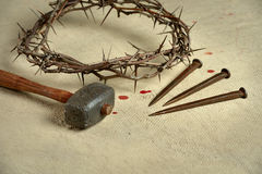Crown of Thorns with nails and Mallet. Christian symbols of the crucifixion with crown of thorns, nails and mallet on distressed cloth stock photos