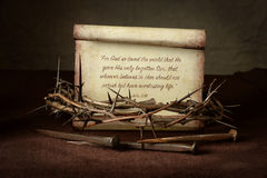 Crown of Thorns and Nails With Scripture. Bible Scripture with crown of thorns and nails over cloth - John 3:16 Stock Photo
