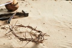 Crown of Thorns religious Easter background. On sand with copy space and nails, hammer, spear and sponge in the background Stock Images