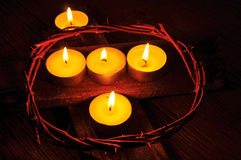 A crown of thorns and some lit candles on a wooden cross Stock Images