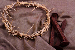 Crown of Thorns & Spikes. A woven crown of thorns and rusty spikes on a woven cloth. Used in the Crucifixion of Jesus. Easter symbols. Selective focus Stock Images