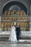 Crowned bride and groom stand in the church behind the priests Stock Images