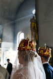 Crowned bride and groom stand in the church Stock Photos