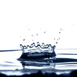 Crowning Glory. A water crown caused by a water droplet falling into a bowl of water stock image