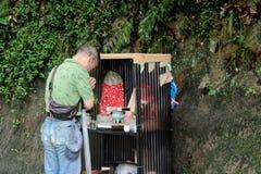 Croyance de respect de vieil homme à l'image de Bouddha de forêt, parc de Nunibiki photos stock