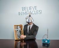 Croyez au texte de miracles sur le tableau noir avec l'homme d'affaires Images libres de droits