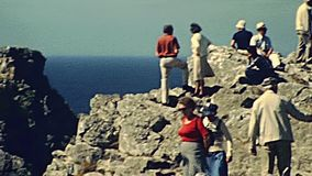 Pointe de Pen Hir. Crozon peninsula, FRANCE - July 15, 1976: tourists in vintage dress on a guided tour at the overlook on top of Pointe de Pen-Hir hill in the stock footage