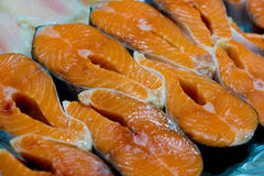 Cru découpé en tranches, saumons non cuits, poissons rouges, se situant dans la glace sur le compteur dans le supermarché frais Photos libres de droits