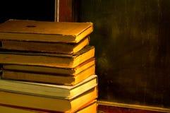 Cru, livres antiques à côté de vieux tableau noir à l'école peinte Photographie stock