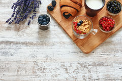 Cruasán, bayas, copos de maíz y taza de leche en una tabla de madera Imagenes de archivo