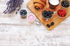 Cruasán, bayas, yogur y taza frescos de leche en una tabla de madera Imagenes de archivo