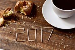 Cruasán, café y número 2017, como el Año Nuevo Fotografía de archivo libre de regalías