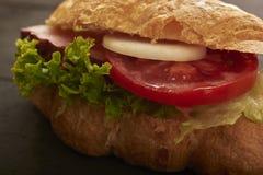 Cruasán con cierre del tomate y de la ensalada del jamón Imagenes de archivo