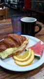 Cruasán del desayuno con café y fruta Foto de archivo