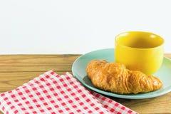 Cruasán en plato verde con blanco de alternancia amarillo del rojo del café y de la tela de la taza Foto de archivo
