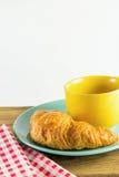 Cruasán en plato verde con blanco de alternancia amarillo del rojo del café y de la tela de la taza Foto de archivo libre de regalías