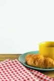 Cruasán en plato verde con blanco de alternancia amarillo del rojo del café y de la tela de la taza Imagen de archivo libre de regalías