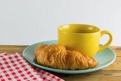 Cruasán en plato verde con blanco de alternancia amarillo del rojo del café y de la tela de la taza Imagen de archivo
