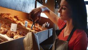 Cruasán femenino del embalaje del panadero metrajes