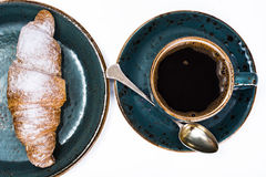 Cruasán fresco con una taza de café caliente Imagen de archivo