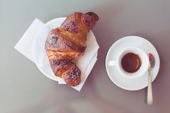 Cruasán fresco en una placa con la taza de café Foto de archivo