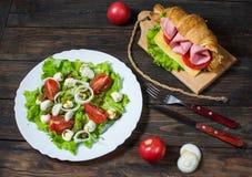 Cruasán ligero y caluroso del desayuno de la primavera con el jamón, el queso, los tomates frescos y la ensalada con la mozzarell Imagen de archivo
