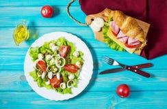 Cruasán ligero y caluroso del desayuno de la primavera con el jamón, el queso, los tomates frescos y la ensalada con la mozzarell Imagen de archivo libre de regalías