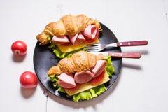 Cruasán ligero y caluroso del desayuno de la primavera con el jamón, queso, tomates frescos en una tabla de piedra blanca Imagen de archivo libre de regalías