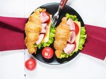 Cruasán ligero y caluroso del desayuno de la primavera con el jamón, queso, tomates frescos en una tabla de piedra blanca Imagen de archivo