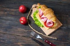 Cruasán ligero y caluroso del desayuno de la primavera con el jamón, queso, tomates frescos en una tabla de piedra de madera Imagenes de archivo