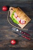 Cruasán ligero y caluroso del desayuno de la primavera con el jamón, queso, tomates frescos en una tabla de piedra de madera Fotografía de archivo libre de regalías