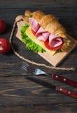Cruasán ligero y caluroso del desayuno de la primavera con el jamón, queso, tomates frescos en una tabla de piedra de madera Imagen de archivo