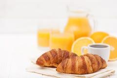 Cruasán recientemente cocido, zumo de naranja, frutas frescas, taza de café en el fondo de madera blanco Desayuno francés fresco Imagenes de archivo