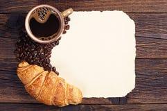 Cruasán, taza de café y papel viejo Fotografía de archivo libre de regalías