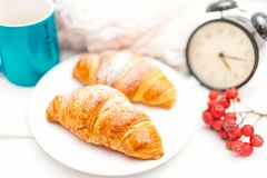 Cruasán y café como desayuno en cama el domingo temprano Foto de archivo libre de regalías