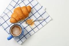 Cruasán y taza de café sabrosos en fondo ligero, Imágenes de archivo libres de regalías