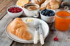 Cruasanes con café, mantequilla, atasco y frutas frescas Imagenes de archivo