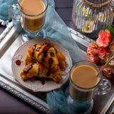 Cruasanes con el chocolate y el café en la bandeja Foto de archivo libre de regalías