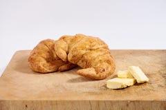 Cruasanes del trigo integral con mantequilla en la tabla de cortar de madera/el fondo de madera del blanco de la tajadera Fotografía de archivo
