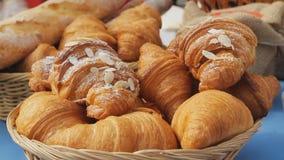 Cruasanes dulces en una cesta en la tabla Fondo del desayuno con los cruasanes de la almendra Cruasanes frescos deliciosos almacen de metraje de vídeo